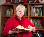 Female senior is reading Stock Images