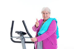 Female senior with thumb up train with fitness machine Royalty Free Stock Photography