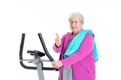 Female senior with thumb up train with fitness machine Stock Photo