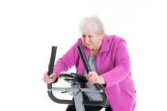 Female senior with thumb up train with fitness machine Stock Photos