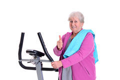 Female senior with thumb up train with fitness machine Stock Images
