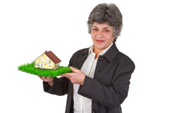 Female senior with toy house Royalty Free Stock Photos
