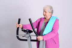 Female senior train with fitness machine. Gray-haired female senior train with fitness machine royalty free stock photography