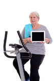 Female senior train with fitness machine and showing tablet PC Royalty Free Stock Images