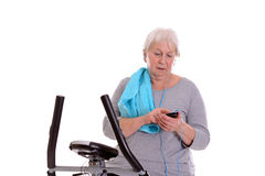 Female senior train with fitness machine and using phone Royalty Free Stock Image