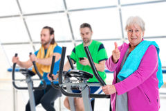 Female senior train with fitness machine and using phone Stock Images