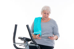 Female senior train with fitness machine and using tablet PC. Gray-haired female senior train with fitness machine and using tablet PC royalty free stock image