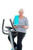 Female senior train with fitness machine and using tablet PC. Gray-haired female senior train with fitness machine and using tablet PC stock photo