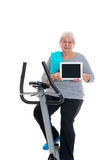 Female senior train with fitness machine and using tablet PC Stock Images