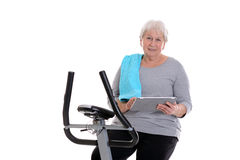 Female senior train with fitness machine and using tablet PC Royalty Free Stock Photo
