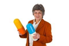 Female senior with two big size pills Royalty Free Stock Photos