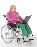 Female senior in wheelchair with computer Stock Images