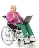 Female senior in wheelchair with computer. Female senior in wheelchair using a computer Stock Photos