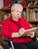 Female senior in wheelchair. Writing a letter Royalty Free Stock Photo