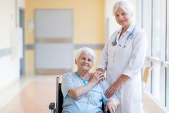 Senior woman in wheelchair with female doctor in hospital stock photography