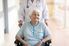 Senior woman in wheelchair with female doctor in hospital stock image