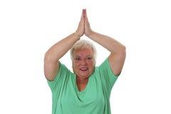 Female senior in yoga meditating. Isolated on white background Royalty Free Stock Photos