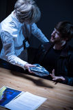 Female sergeant talking with suspect. In interrogation room royalty free stock photo
