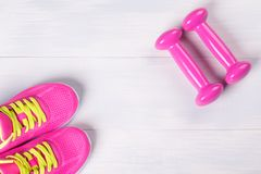 Female set for playing sports, with pink dumbbells, on a light wooden floor Stock Photography