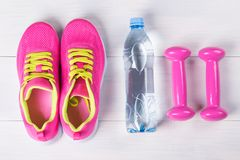 Female set for playing sports, with pink dumbbells, on a light wooden floor, and a bottle of water. Female set for playing sports, with pink dumbbells, on a Royalty Free Stock Image