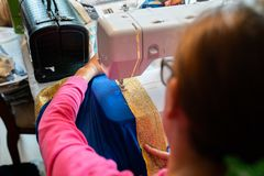 Female sewing a Halloween kid costume on the machine. stock images