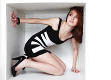 Female in sexy black dress. Lying in white cube Stock Photo
