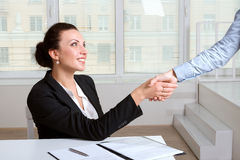 Female shakes hands sitting at the table Royalty Free Stock Photo