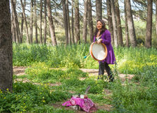 Shaman drumming horizontal altar. Female shaman drumming and chanting with altar in foreground in a wooded setting Stock Photos