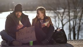 Female sharing sandwich and talking to homeless. Lonely begging homeless man sitting on street at sunset at river bank while young woman passing by, sits near stock footage