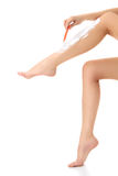 Female shaves her legs Stock Photography