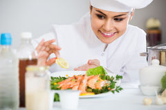 Female shef with herbs and shrimps dish Stock Photo