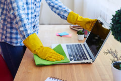 Female in shirt and gloves dusting laptop Stock Photos