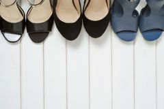 Female shoes background. Female shoes on a white wooden background Royalty Free Stock Photo