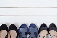 Female shoes background. Female shoes on a white wooden background Royalty Free Stock Photos