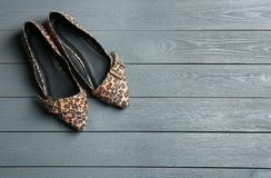 Female shoes with leopard print on wooden background, top view. Space for text stock photos