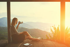 Female is shooting video on smart phone,while is sitting against subtropical landscape Royalty Free Stock Photos