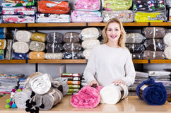 Female shop assistant demonstrating assortment of home textiles Stock Image