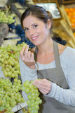 Female shop assistant eating grape Stock Photo