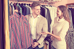Female shop assistant helping customer to choose shirt in men' Stock Image