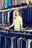 Female shop assistant helping customer to choose suit Stock Photos