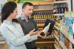 Female shop assistant helping male customer at supermarket Royalty Free Stock Photo