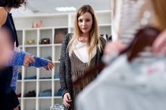 Female shop assistant offering two items of clothes to the customers in fashion store.  Royalty Free Stock Photography