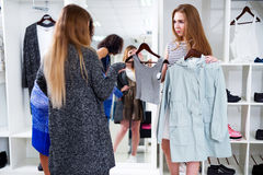 Female shop assistant offering two items of clothes to the customers in fashion store.  Stock Photo
