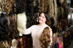 Female shop assistant selling natural hail ponytails Royalty Free Stock Image