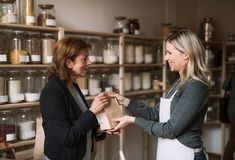 A female shop assistant serving a senior customer in a zero-waste shop. A young female shop assistant serving a senior customer in a zero-waste shop royalty free stock images