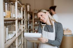A female shop assistant with smartphone working in a zero-waste shop. stock photos