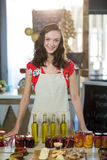 Female shop assistant standing at the counter with pickle, olive oil and jam bottles. At grocery shop Stock Image