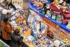 Female shop assistants selling Christmas decorations in central. MOSCOW - 30 NOVEMBER, 2017: Female shop assistants dressed as Snow Maidens for Christmas sales royalty free stock image