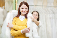 Female shop consultant helps girl chooses fur cape. At shop of wedding fashion. Focus on bride Stock Image