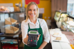 Female shop owner holding credit card reader Royalty Free Stock Image